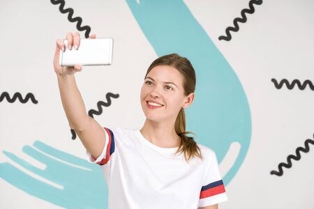 Young beautiful woman standing on white art background with smartphone in hand, taking selfie photo
