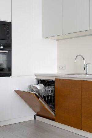 Vertikales Foto des eingebauten Backofens in der Nähe der geöffneten modernen Spülmaschine mit weißen Tellern und sauberen Tassen in der Küche Standard-Bild