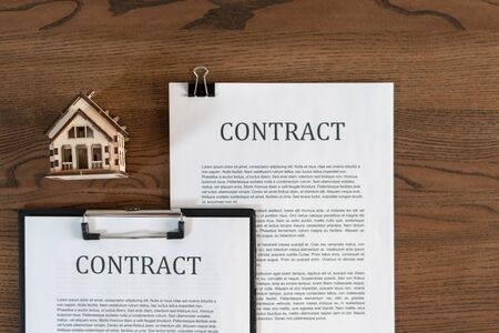 Top view symbol of house near contract or agreement in clipboard on wooden table in office