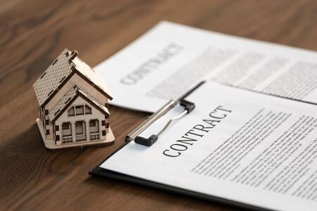 Selective focus of wooden house near contract or agreement in clipboard. Document on textured table in office Imagens
