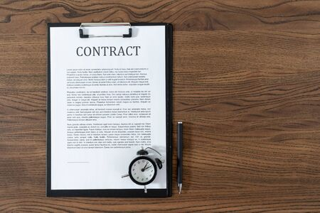 Top view of contract, alarm clock and stationery pen at wooden table with copy space