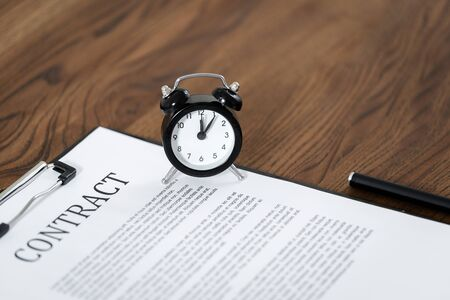 Selective focus of contract, alarm clock and stationery pen at wooden table with copy space