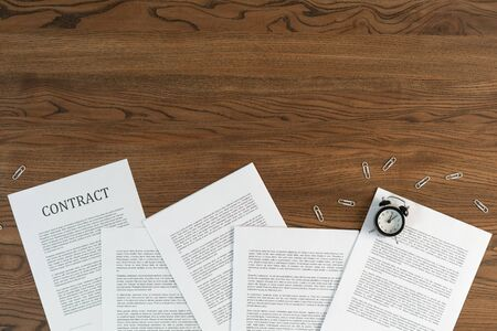 Top view of contract, alarm clock and stationery paperclip at wooden table with copy space Imagens