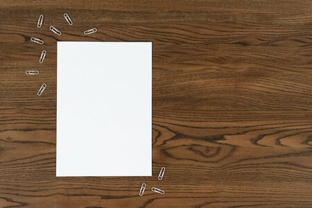 Top view of white empty paper blank and stationery paperclip on wooden table with copy space Imagens