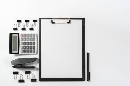 Top view of empty paper blank in clipboard, calculator, stapler and stationery isolated on white background with copy space Imagens