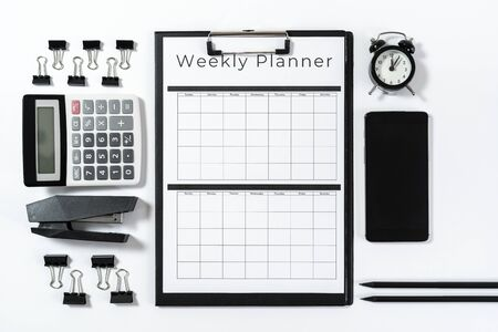 Top view of weekly planner in clipboard, calculator, stapler, alarm clock, smartphone, pencil and stationery isolated on white background with copy space