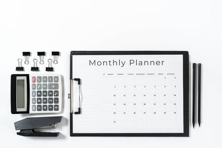 Top view of weekly planner in clipboard, calculator, alarm clock, smartphone, pencil and stationery isolated on white background with copy space Imagens