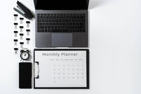 Top view of monthly planner in clipboard, laptop, smartphone, alarm clock, paperclip and stationery isolated on white background with copy space