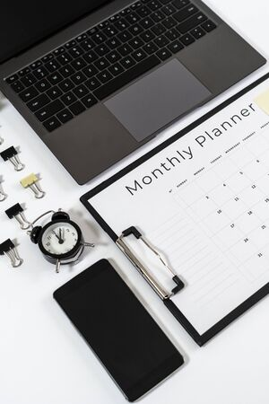 Flat lay of monthly planner in clipboard, laptop, smartphone, alarm clock, paperclip and stationery isolated on white background with copy space