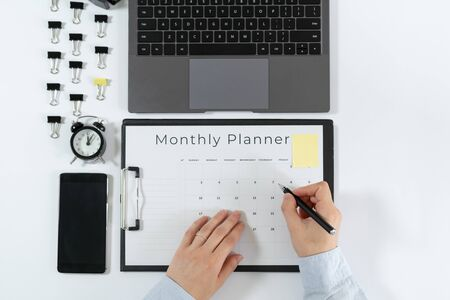 Top view of woman making notes in monthly planner. Laptop, smartphone, alarm clock, paperclip and stationery isolated on white background with copy space Stock Photo
