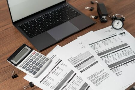 Modern laptop computer, documents, financial bills, alarm clock, calculator and stationery on wooden table in office