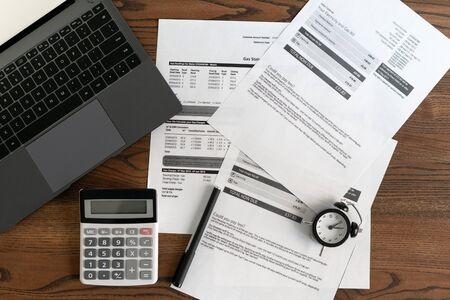 Widok z góry laptopa, dokumentów, rachunków finansowych, budzika, kalkulatora i artykułów piśmiennych na drewnianym stole w biurze