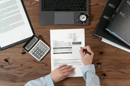Top view of bookkeeping woman working with bills, counting savings and investment on calculator, sitting at office behind wooden table