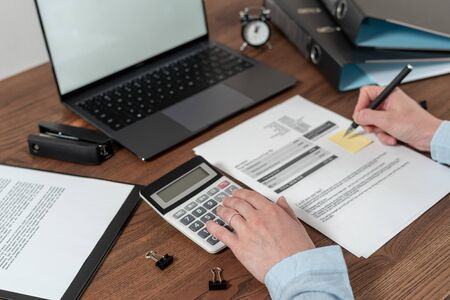 Cropped view of young adult woman working with bills, counting tax and income on calculator, sitting at office behind wooden table with laptop