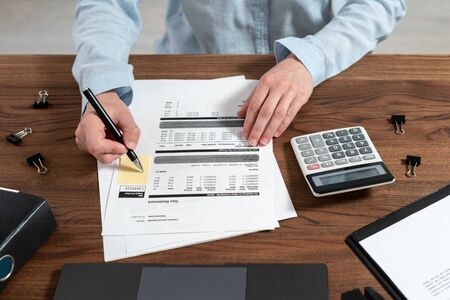 Cropped view of bookkeeping woman working with bills, counting savings and investment on calculator, sitting at office behind wooden table Imagens