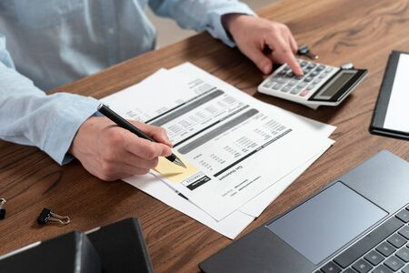 Cropped view of businesswoman working with bills, documents, counting savings, tax, income and investment on calculator, sitting at office behind wooden table