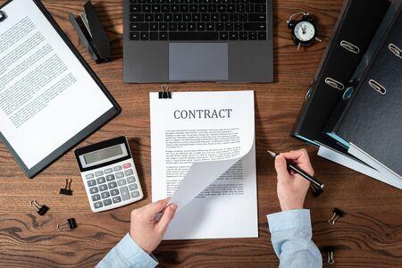 Draufsicht der Geschäftsfrau, die Notizen im Vertrag macht, Vereinbarung liest, im Büro hinter Holztisch mit Laptop, Dokumenten, Ordnern und Schreibwaren sitzt