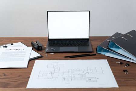 Modern laptop computer with blank screen and copy space at workplace. Documents, architecture plan and stationery on wooden table in office Imagens