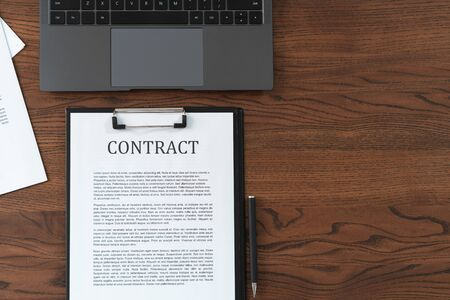 Top view of contract in clipboard lying at office near laptop, on textured and wooden table with copy space