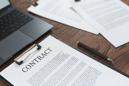 Contract in clipboard lying at office on wooden table with  laptop and documents Imagens