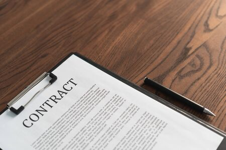Contract in clipboard lying at office on wooden table with copy space and black pen for signature