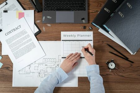 Top view of engineer designer working with weekly planner, sitting in office with laptop computer, architecture plan, blueprint and documents on wooden table Stock Photo
