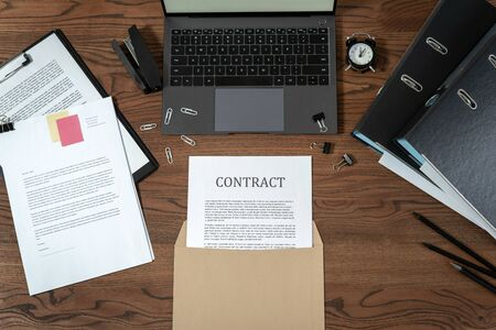 Top view of contract in envelope, documents, laptop computer and stationery on wooden table in modern office at workplace