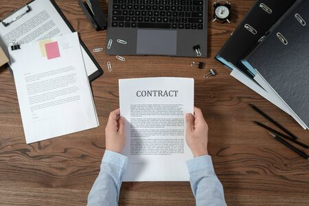 Top view of businesswoman holding contract in hands. Documents, laptop computer and stationery on wooden table in modern office Stock Photo