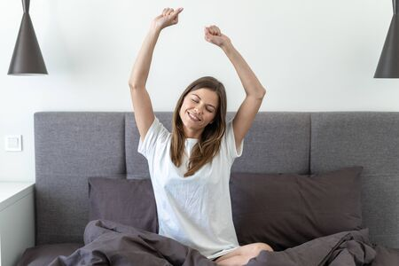 Young adult woman with closed eyes smiling, stretching, sitting on bed, resting at morning and spending free time in bedroom