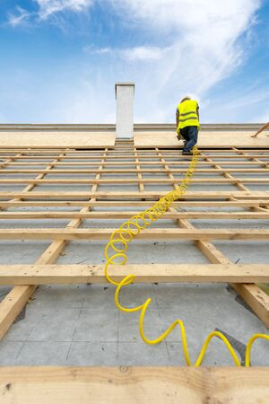 Concept of house under construction. Vertical photo of mature builder standing on rooftop of modern building with pneumatic nailgun in hands. Unrecognizable man working against blue sky on background Фото со стока