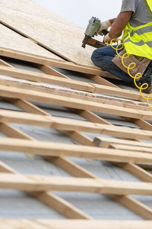 Concept of building construction industry. Cropped, unrecognizable mature and professional master in protective uniform wear using air or pneumatic nail gun and working on roof top of new modern house