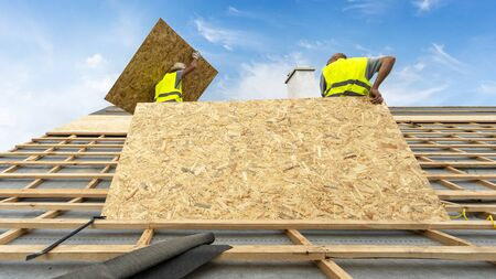 Concept of house under construction. Two professional installer standing on roof top against blue sky on background. Man holding in hands wooden, plywood or osb panel on modern building rooftop