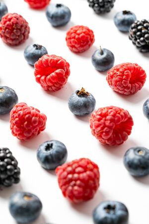 Vertical photo, flat lay composition and close up view of mix ripe, yummy and sweet blueberries, blackberries, raspberries fruits on white background Banque d'images