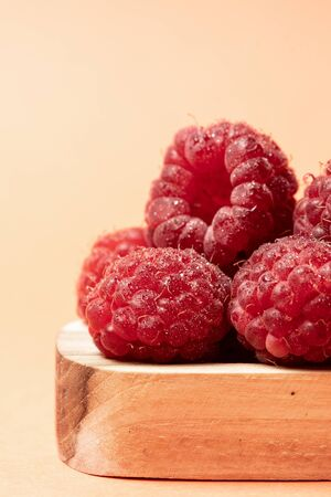 Vertical photo and macro view of red and ripe raspberry fruits in wooden bowl on pastel peach background with copy space Banque d'images
