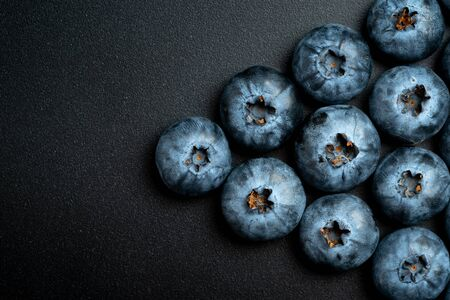 Flat lay and close up composition of ripe blueberries fruit on black background with copy space Banque d'images