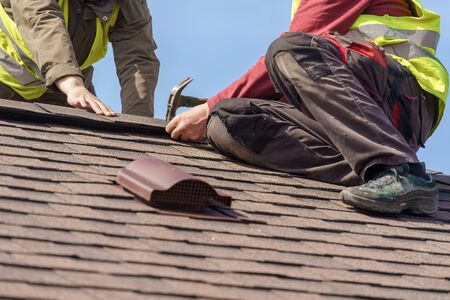 Two mature roofers in protective uniform using helmet and installing asphalt shingle or roof tile on top of new house against blue sky Imagens