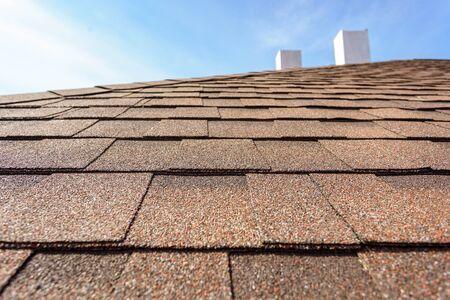 Nahaufnahme Fotoschicht neuer Asphaltschindeln auf dem Dach des neuen Hauses im Bau mit Schornstein und blauem Himmel auf unscharfem Hintergrund