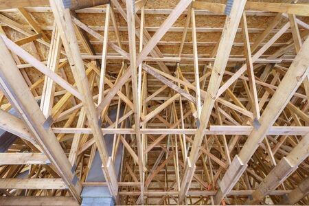 Timber frame house and real estate concept. Low angle top view photo of new build roof attic with wooden truss, post and beam framework