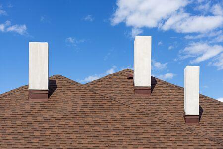 Cerrar foto de tejas de asfalto instaladas con tres chimeneas blancas y nuevas en una casa residencial en construcción contra un fondo azul con espacio para copiar texto Foto de archivo