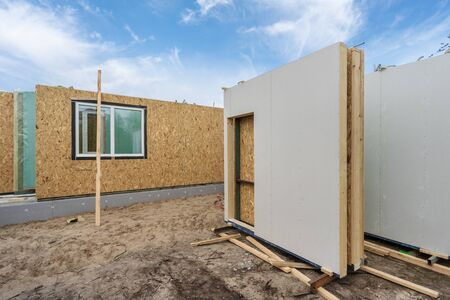 Construction new and modern modular house. Composite sip panels near unfinished building under blue sky