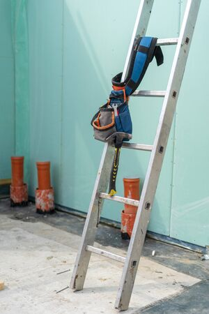 Construction new and modern modular house from composite sip panels. Vertical photo of tool belt with instrument on metal ladder by the wall