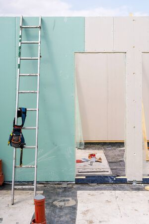 Construction new and modern modular house from composite sip panels. Vertical photo of small toolbelt with equipment and instrument on metal ladder by the wall Stockfoto