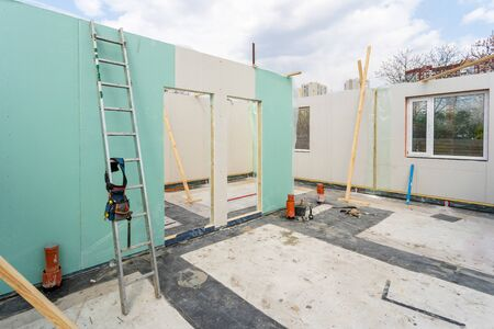 Construction new and modern modular house from composite sip panels. Tool belt with instrument on metal ladder by the wall in unfinished building room against blue sky