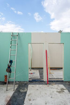 Construction new and modern modular house from composite sip panels. Vertical photo of unfinished room in building with tool belt on metal ladder by the wall