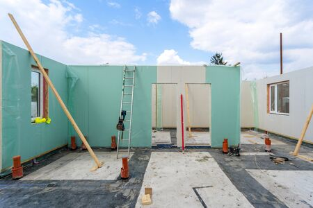 Construction new and modern modular house from composite sip panels. Unfinished room in building against blue sky background