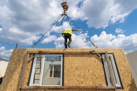 Low angle view of construction new and modern modular house from composite sip panels. Collar worker in protective uniform wear working on building development industry of energy efficient property Stockfoto