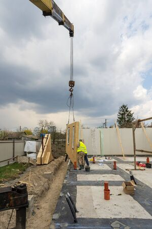 Vertical photo of construction new and modern modular house from composite sip panels. Collar worker in uniform wear working on building development industry of energy efficient property Stockfoto