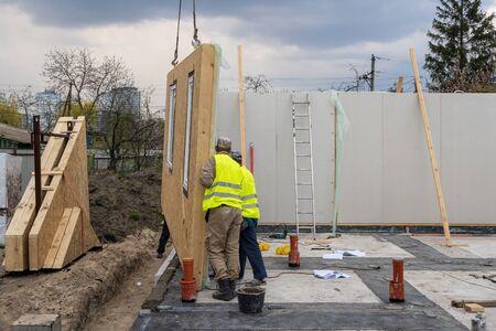 Proces van constructie nieuw en modern modulair huis van composiet sip-panelen. Twee arbeidersman in speciale beschermende uniforme kleding die werkt aan de bouw van de ontwikkelingsindustrie van energiezuinig onroerend goed Stockfoto