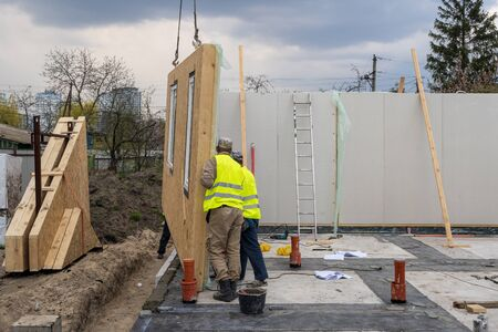 Proceso de construcción de una casa modular nueva y moderna a partir de paneles compuestos. Hombre de dos trabajadores en ropa de uniforme de protección especial que trabaja en la industria de desarrollo de edificios de propiedad de eficiencia energética Foto de archivo