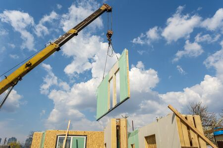 Process of construction new and modern modular house from composite sip panels. Crane with wall part against blue sky background